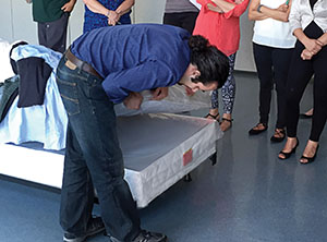 An entomologist demonstrates the inpection of a mattress for bed bugs.