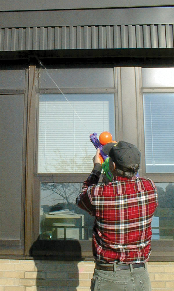 Man using a water gun on a wasp nest