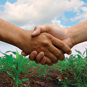 A handshake happens in a farm background.