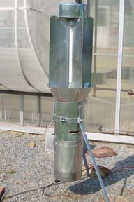 A black light trap, with a shiny metal exterior, stands guard outside a greenhouse.